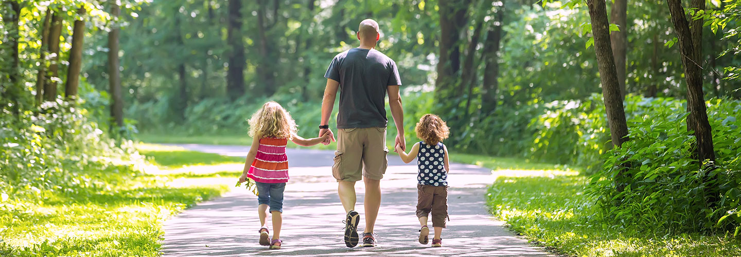 Man walking with two young girls on a park path