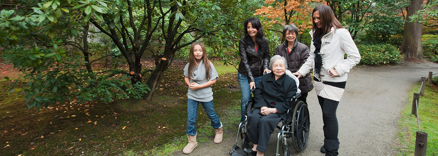 Elderly woman in wheelchair is pushed by three woman and a young girl.